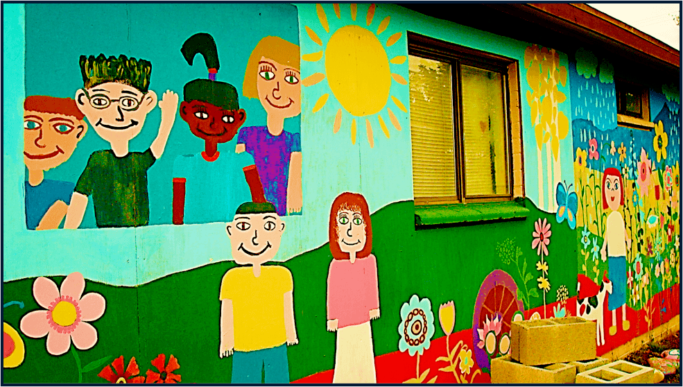 colorful painting on side of a building in a children's style--children, flowers, sunshine